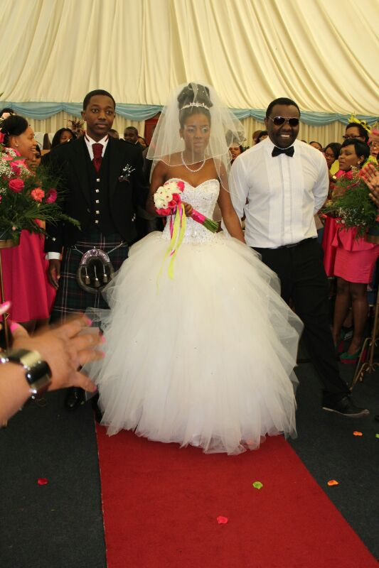 Sandra being walked down the aisle by her two brothers Titi and Tinashe
