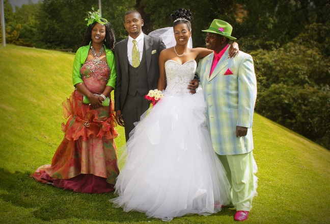 Wedding, caption, (Proud Archbishop and the Prophetess with their new son-in-law nd daughter)